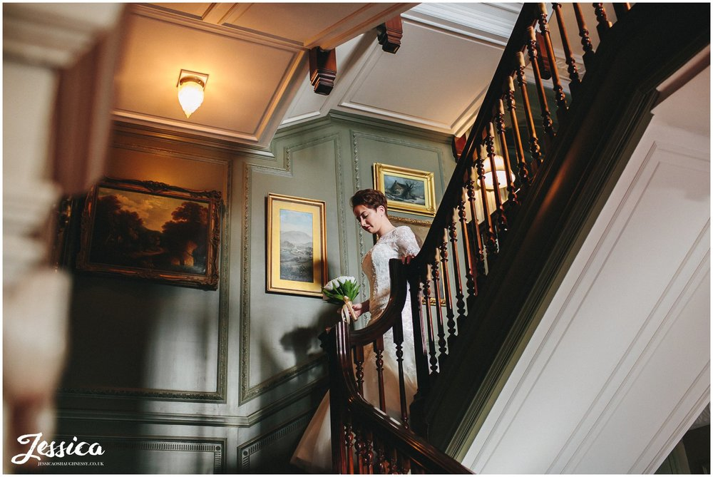 bride walks down the stairs to her ceremony in thornton manor, wirral