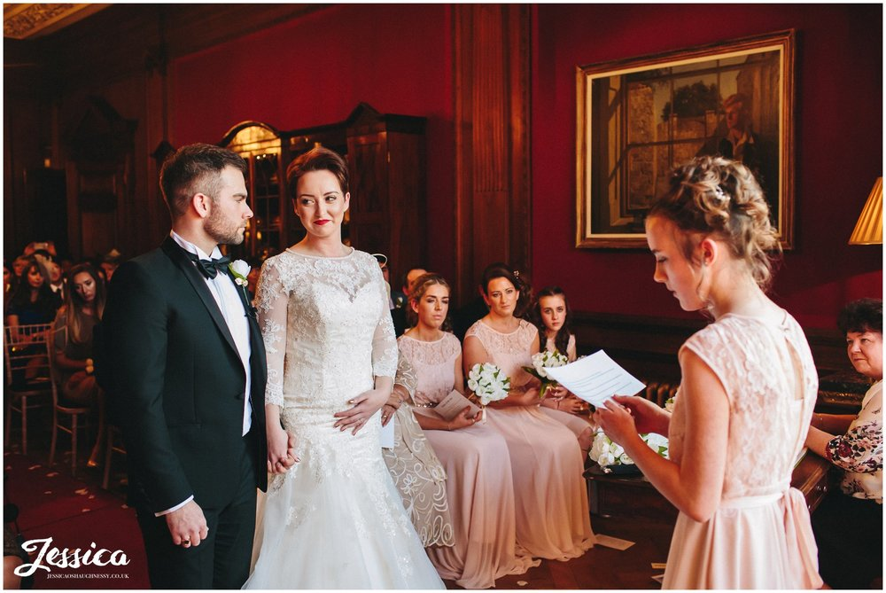 bridesmaid reads touching poem out to the bride & groom at their wirral wedding