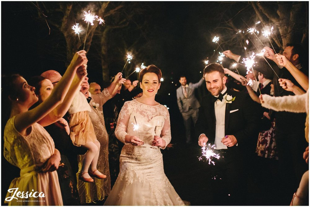 bride & groom walk through their guests holding sparklers in the grounds of thornton manor