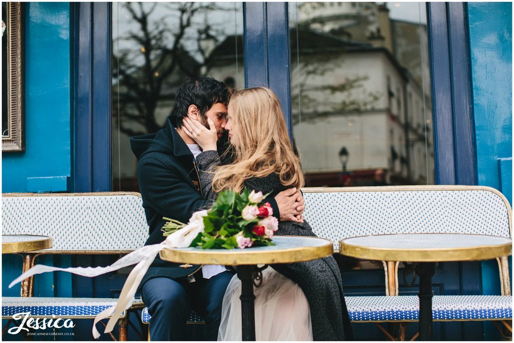 wind blows brides hair as she kisses her groom sitting in a cafe in mont marte