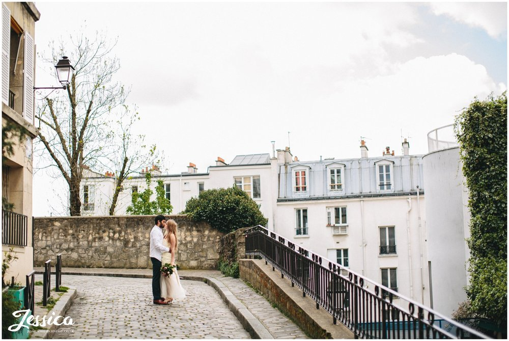 newly weds kiss on parisian street - france wedding photographer