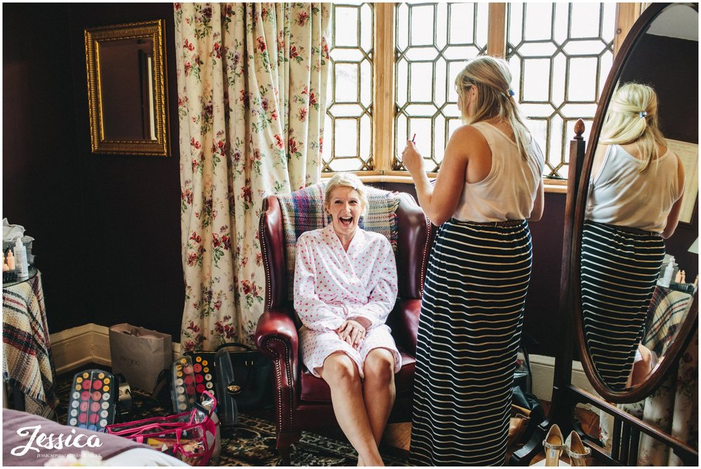 the bride getting ready in the headmasters house at her cholmondeley arms wedding cheshire