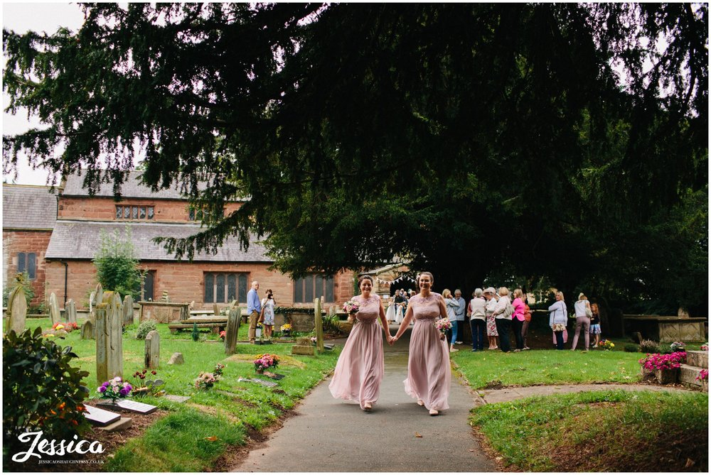 bridesmaids walk to meet the bride as she arrives at st chad's church in farndon