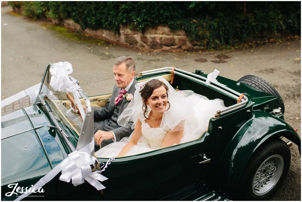 bride in her wedding car arriving at farndon church in chester
