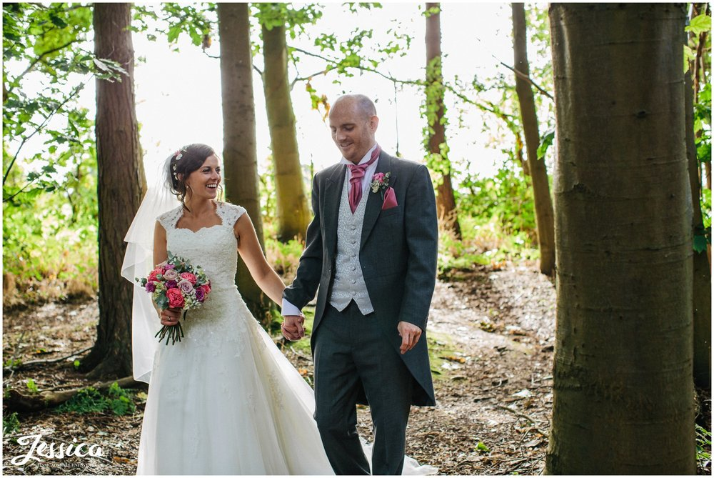 Newly wed's walk through the forest on their wedding day in cheshire