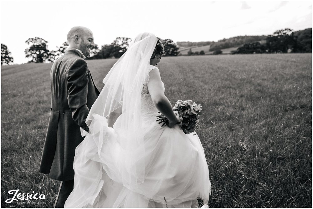 black and white photo of the bride & groom walking through a field at their wedding in cheshire