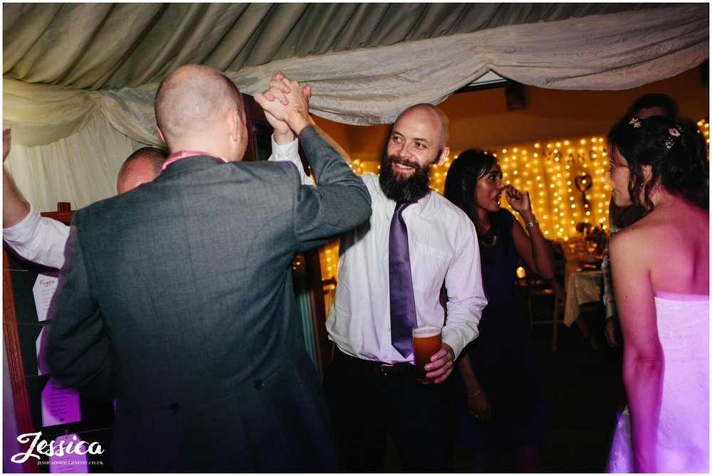 guests hi-5 whilst dancing at a wedding in cheshire