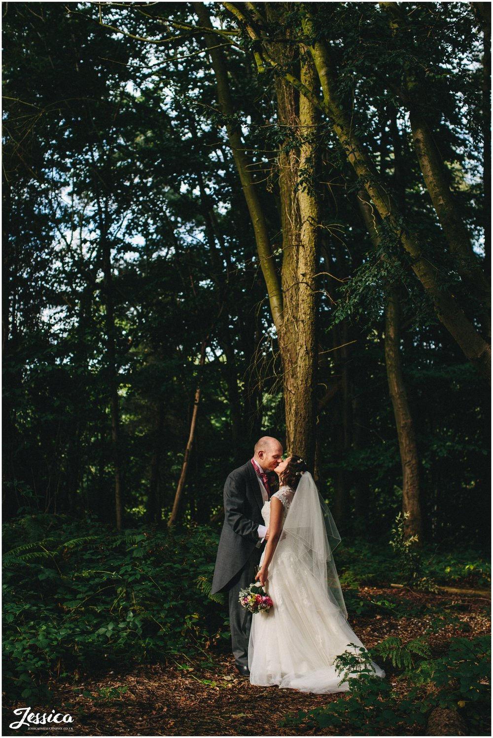 bride & groom kissing in the woodland in chester