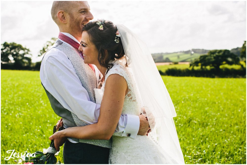 bride & groom embrace in the sunshine at their wedding at harthill weddings, the success factory