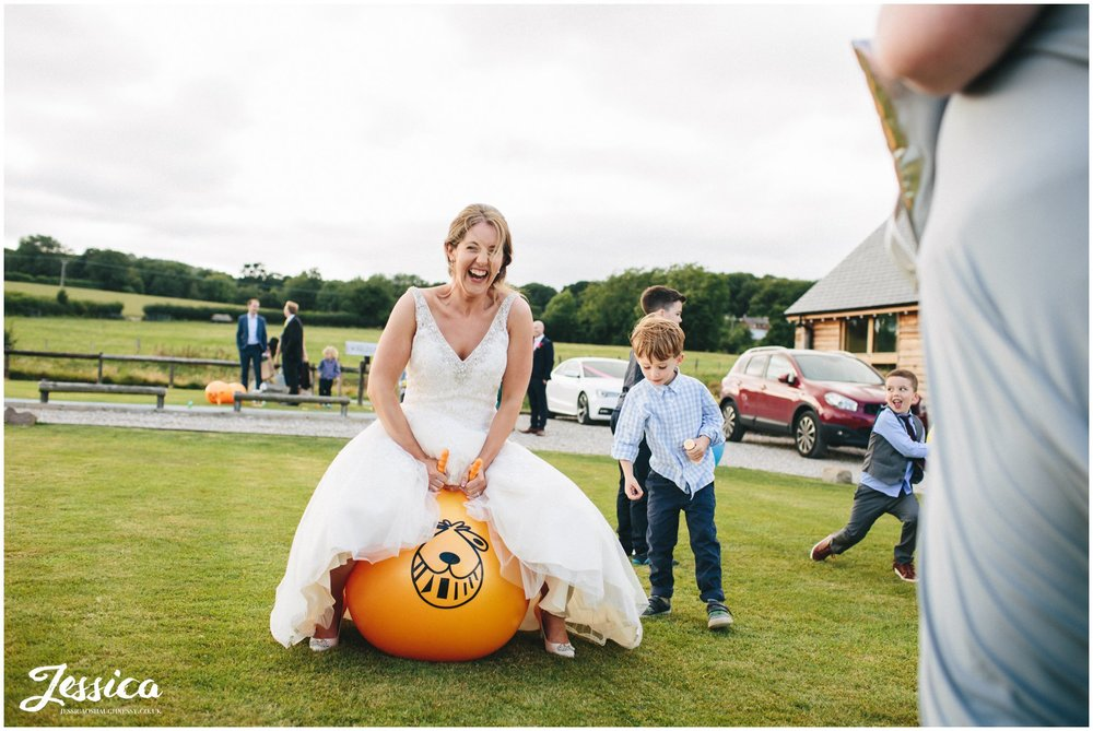 bride plays on space hopper on the lawn outside north wales wedding venue, tower hill barns
