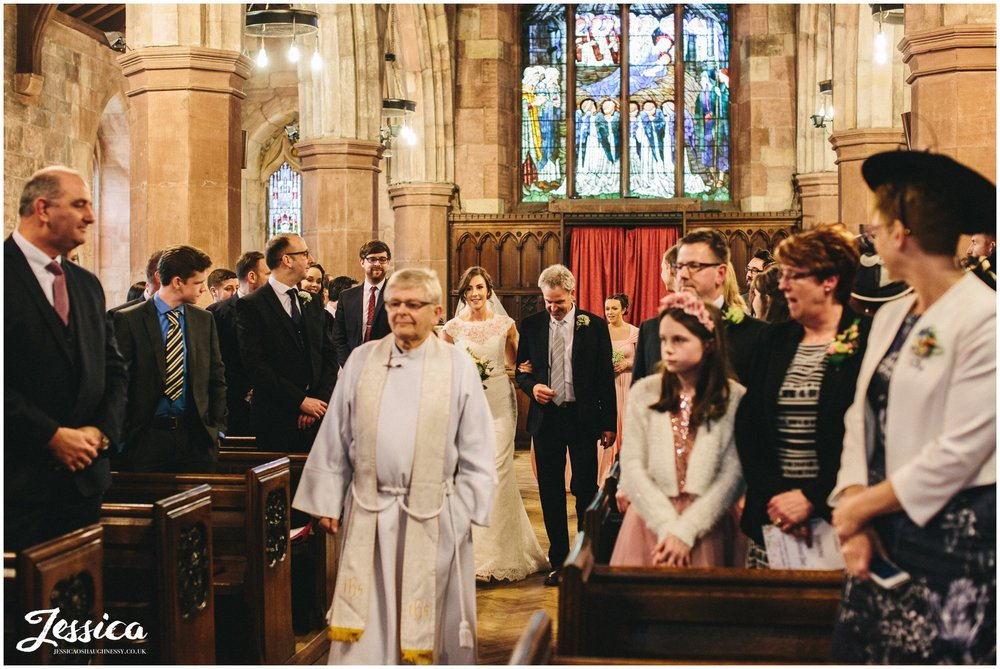 bride walks down the aisle at the north wales church in hawarden