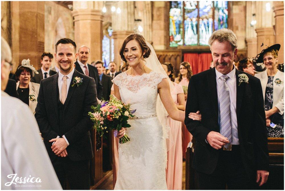 bride links arms with her father during the wedding ceremony, st deiniols church