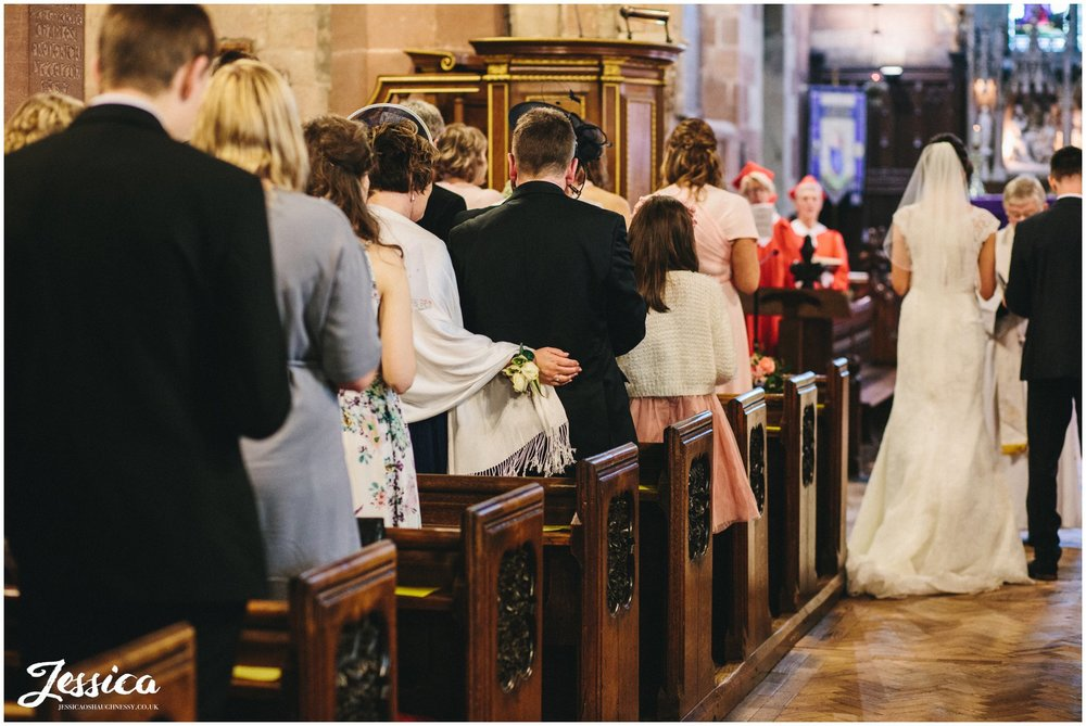 guest puts her arm around her partner during the wedding ceremony