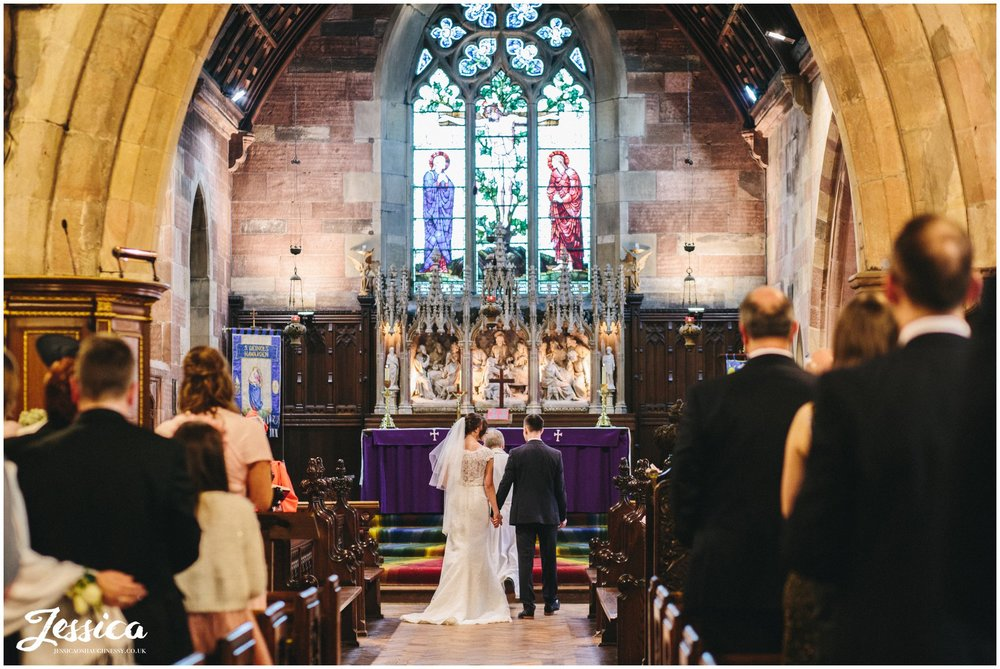 wide shot of the bride & groom taken from the back of st deiniols church