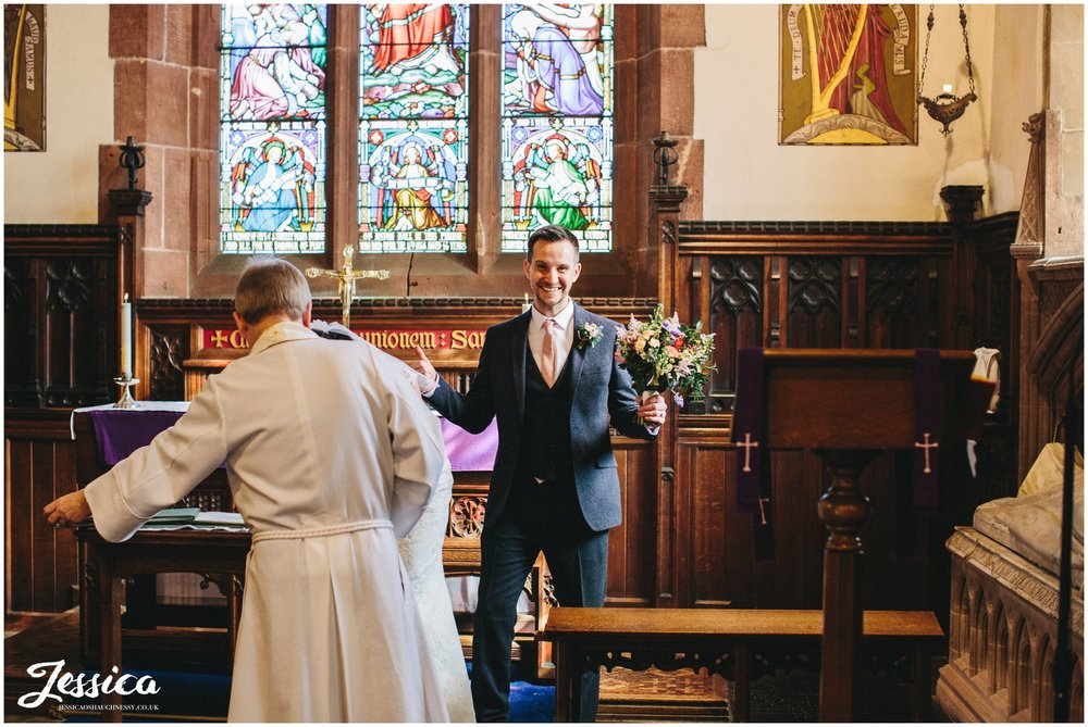 groom holds his brides bouquet whist laughing - north wales wedding