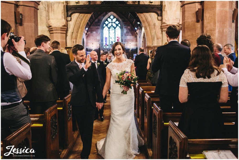newly wed's walk out of the church after their ceremony - st deiniols in hawarden