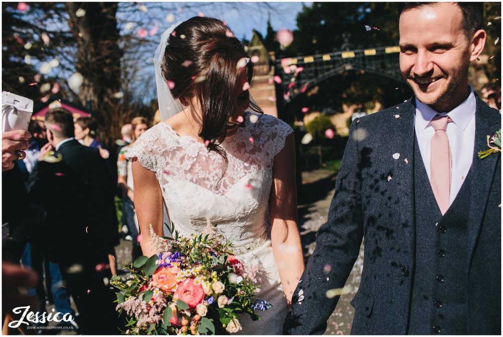 bride and groom are showered in confetti on a sunny day in north wales