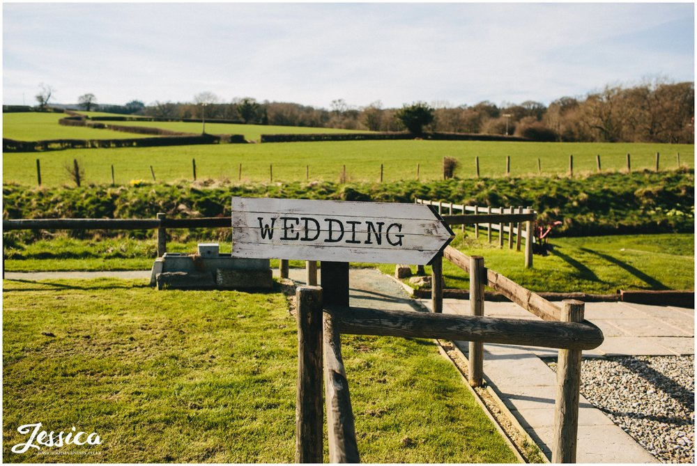 sign pointing wedding guests to the reception at tower hill barns