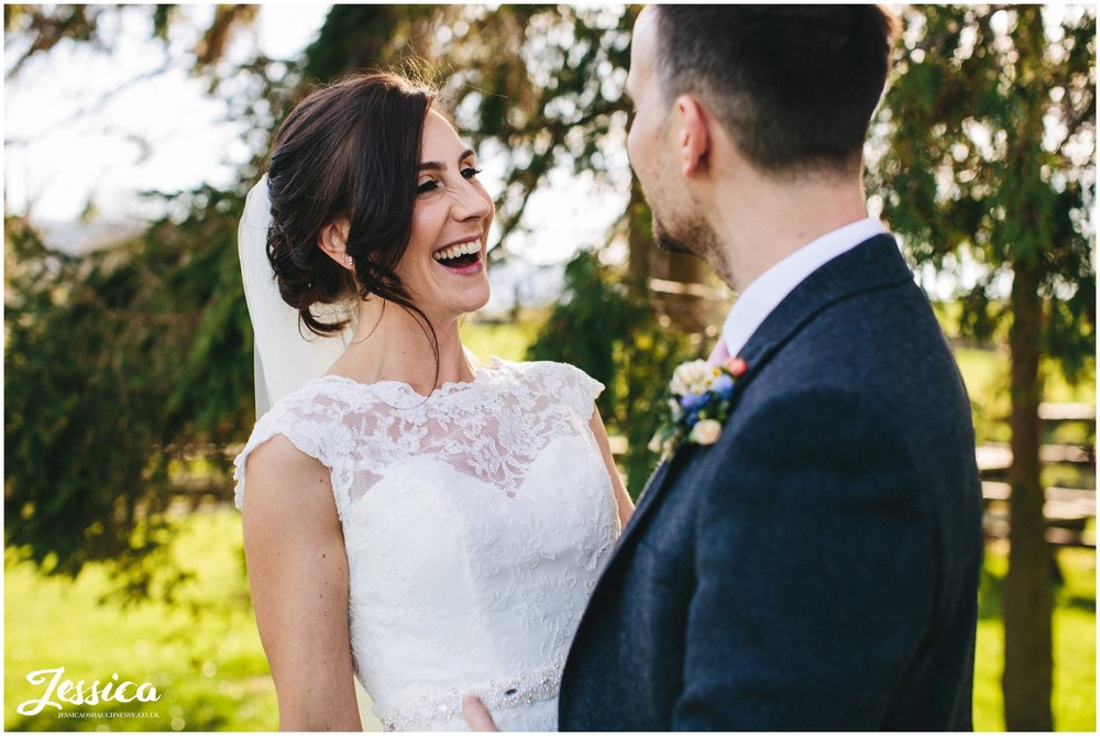 bride laughs stood in front of trees at a north wales wedding