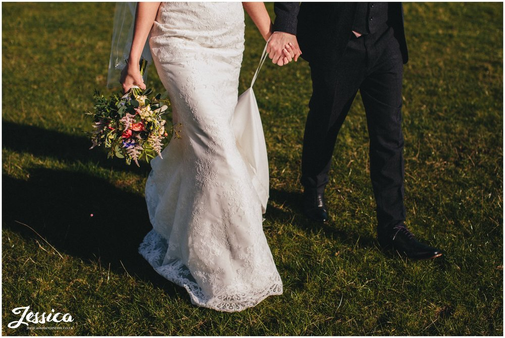 cropped image of bride and groom walking