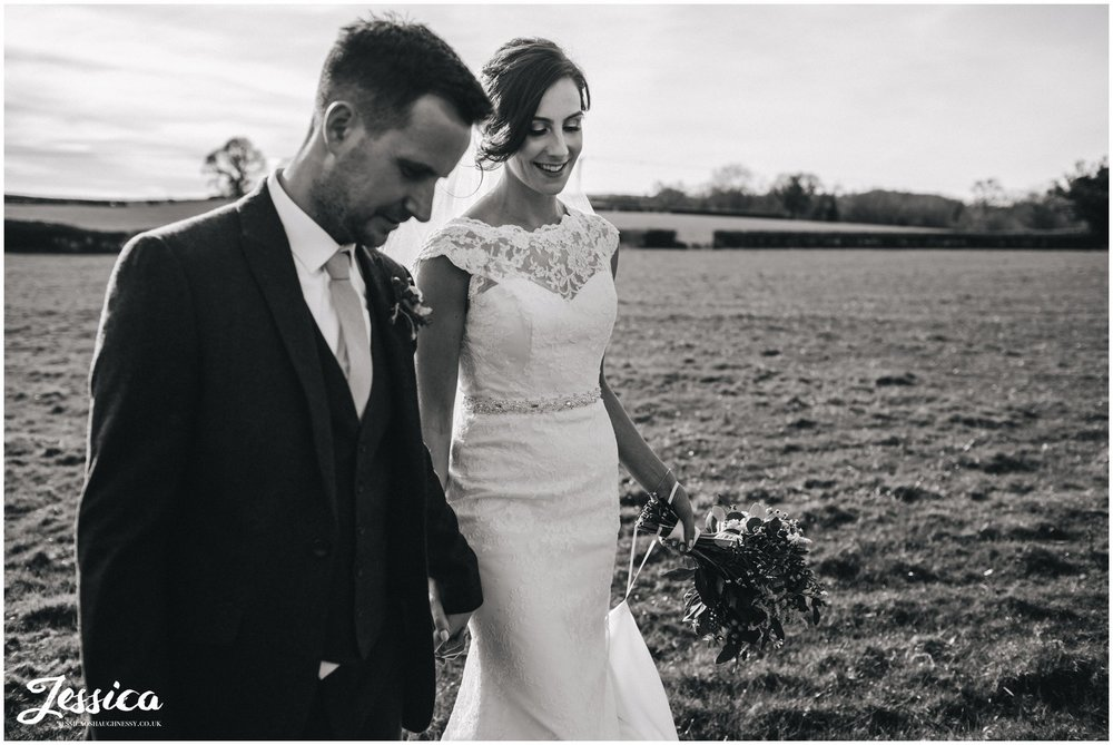 newly wed's wander through field in north wales - black and white