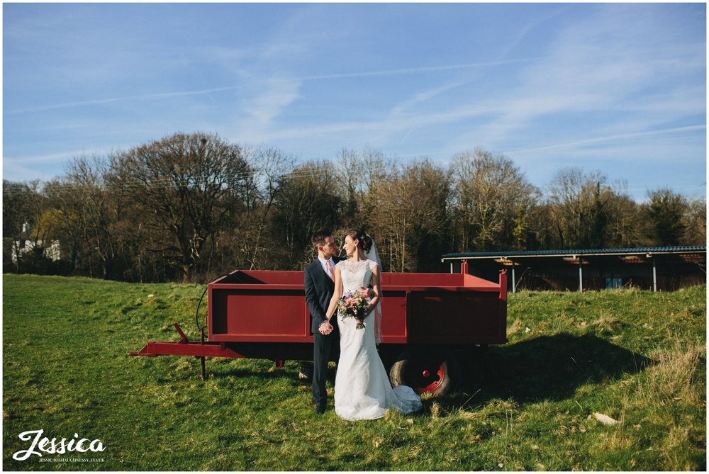 wide shot of newly wed's in front of farming trailer - tower hill barns wedding