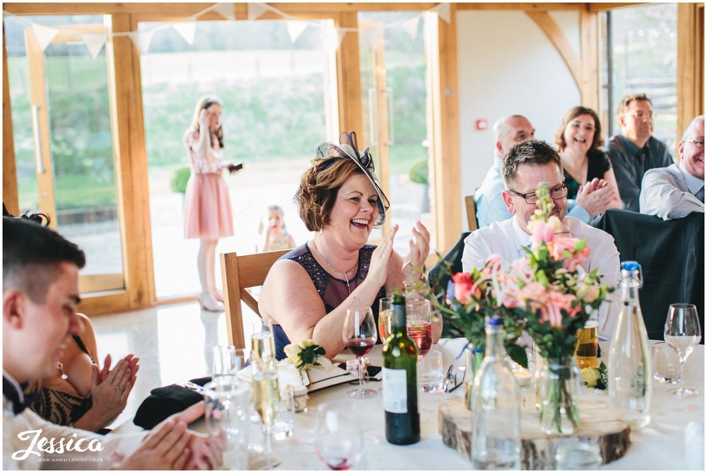 guests laugh as the groom gives his speech on his wedding day in north wales
