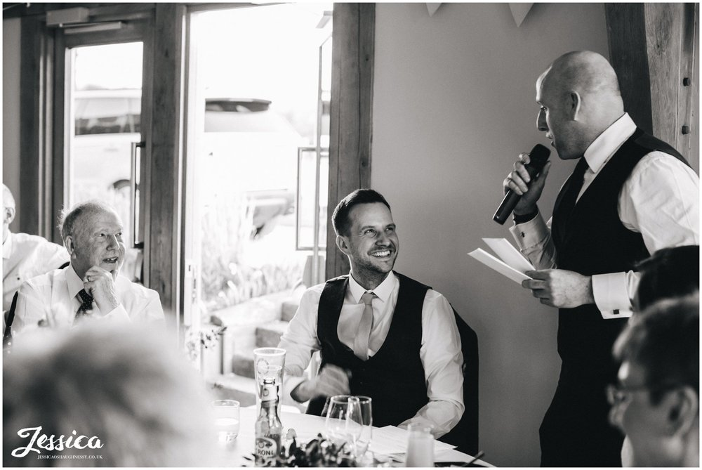 black and white photograph of groom laughing during the speeches in north wales