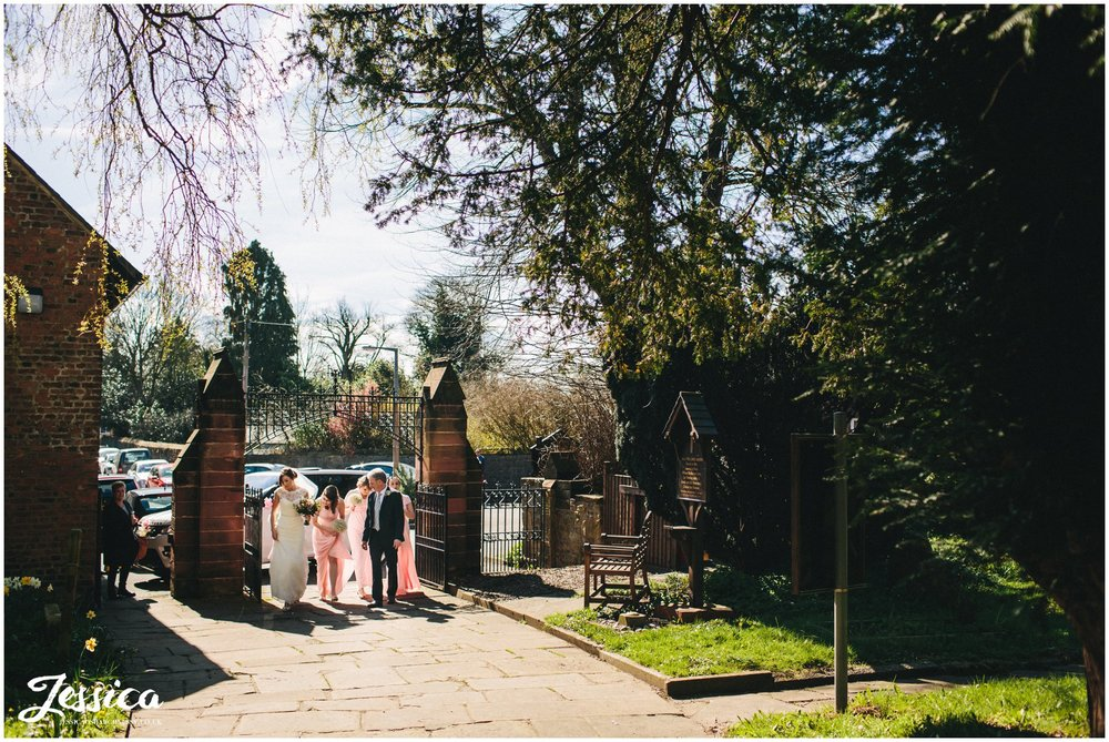 bridal party escort bride up the church path in hawarden