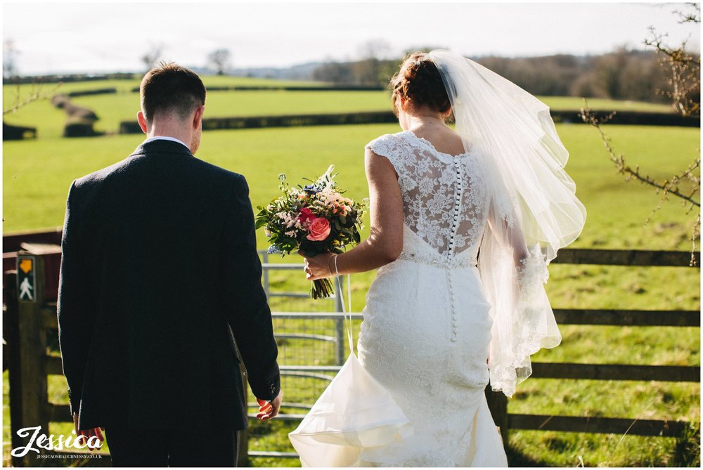 groom helps bride through wooden fence leading to the field in north wales