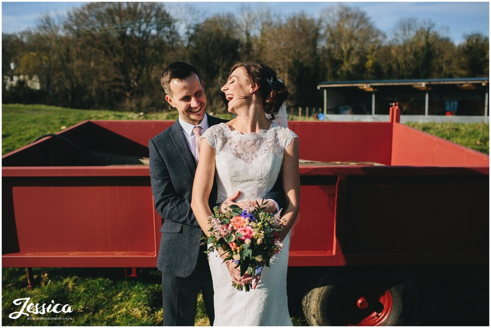 nia & joe in front of red farm trailer on their wedding day at tower hill barns in wrexham