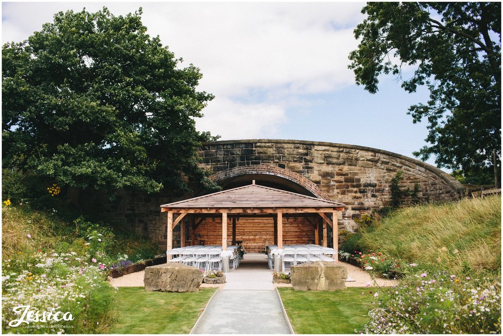 view of the outdoor ceremony space at tower hill barns - wooden cladded bridge