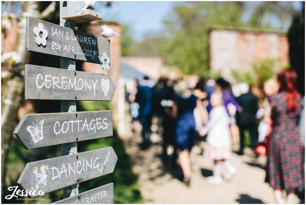 rustic wedding sign points guests to the glass house ceremony