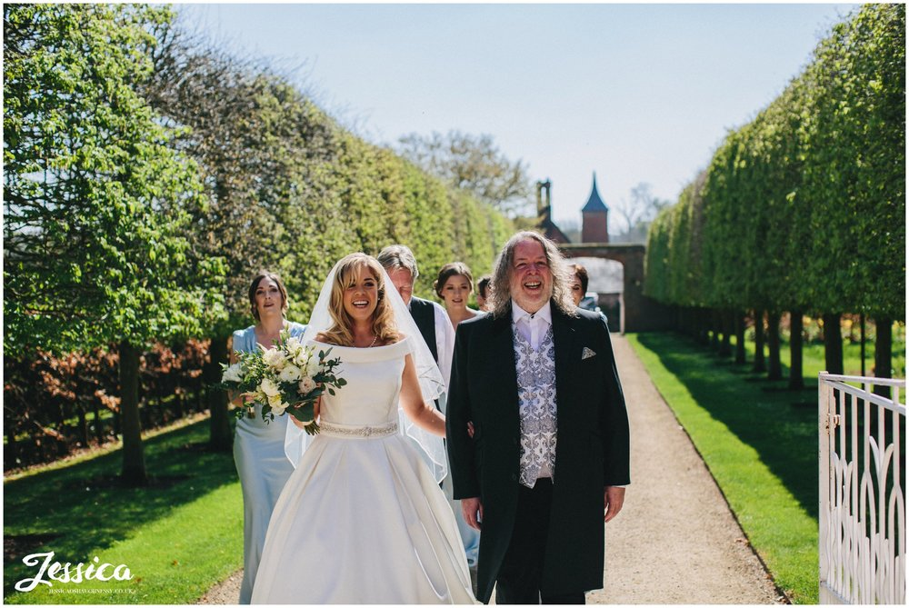bride & her father walk down path at Combermere Abbey to the ceremony in the glasshouse