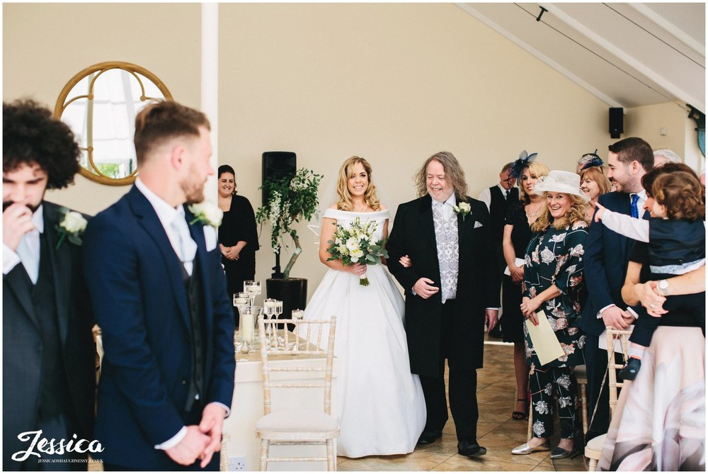 bride enters the glass house and walks down aisle to her groom