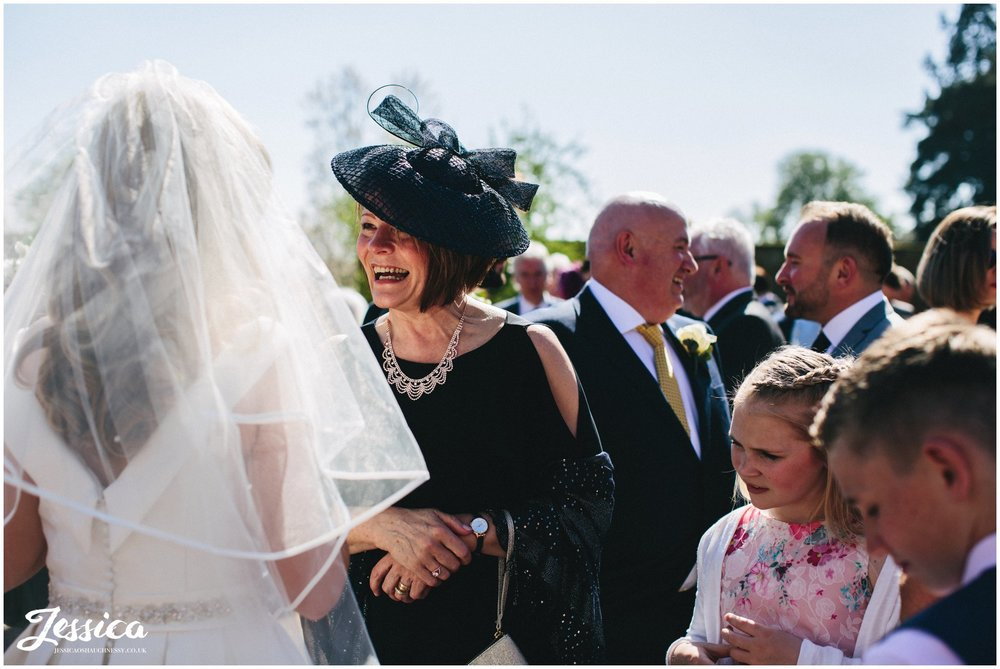 mother of the groom laughs with bride on her wedding day