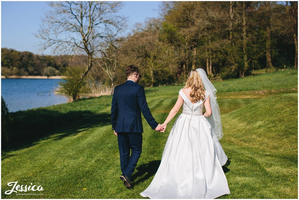 newly wed's hold hands and walk next to the lake