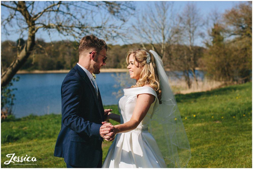 newly wed's hold hands by the lake at Combermere Abbey