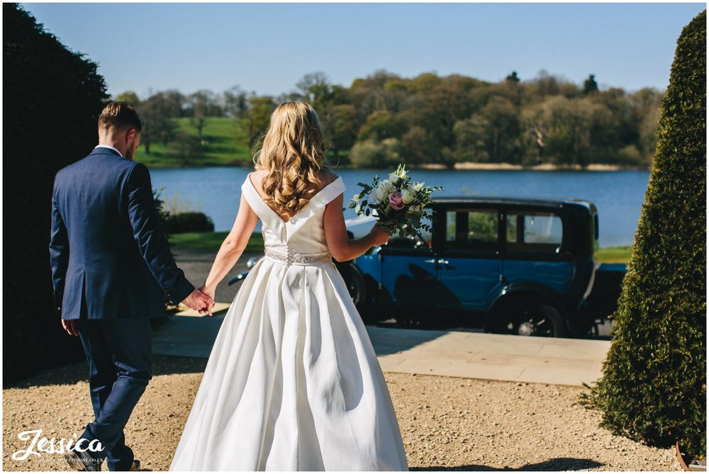 couple walk towards their wedding car at Combermere Abbey in whitchurch