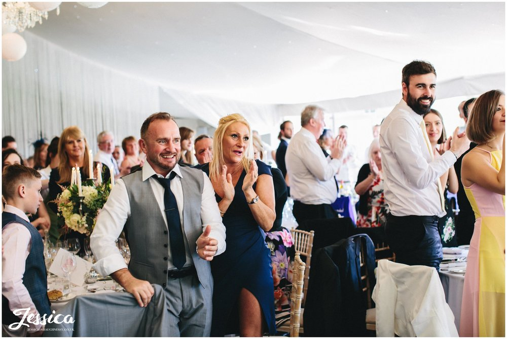 guests applaud newly weds as they get announced in