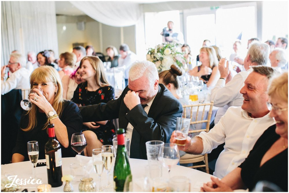 guest laughs into hands during the speeches at Combermere Abbey