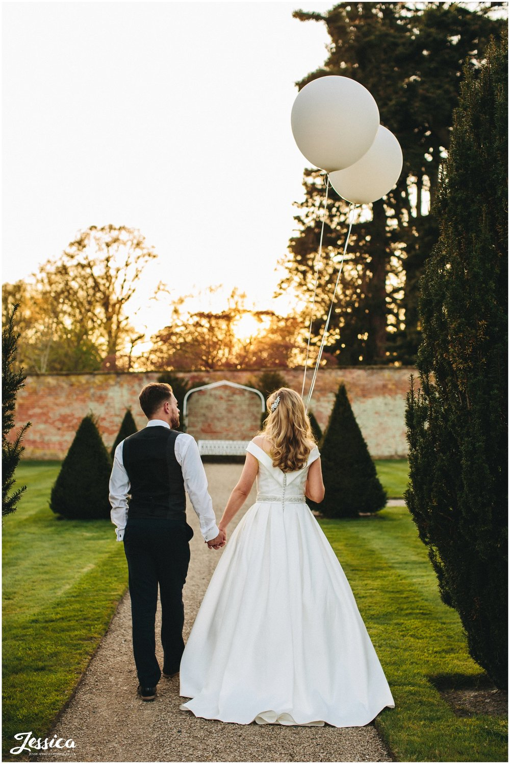newly wed's walk towards sun set holding big white balloons
