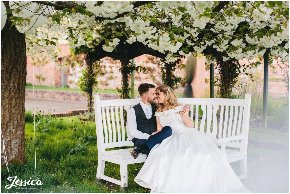 newly wed's kiss on a bench under the blossom trees