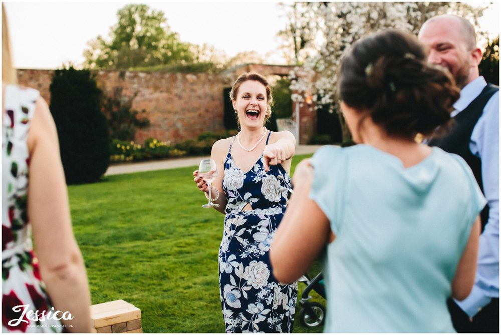 guests point and laugh during a wedding reception at Combermere Abbey