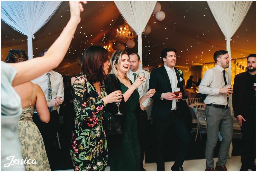 guests laugh on the dancefloor in the pavilion at Combermere Abbey, shropshire