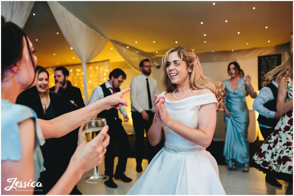 bride dances with bridesmaid during her wedding reception in the pavilion