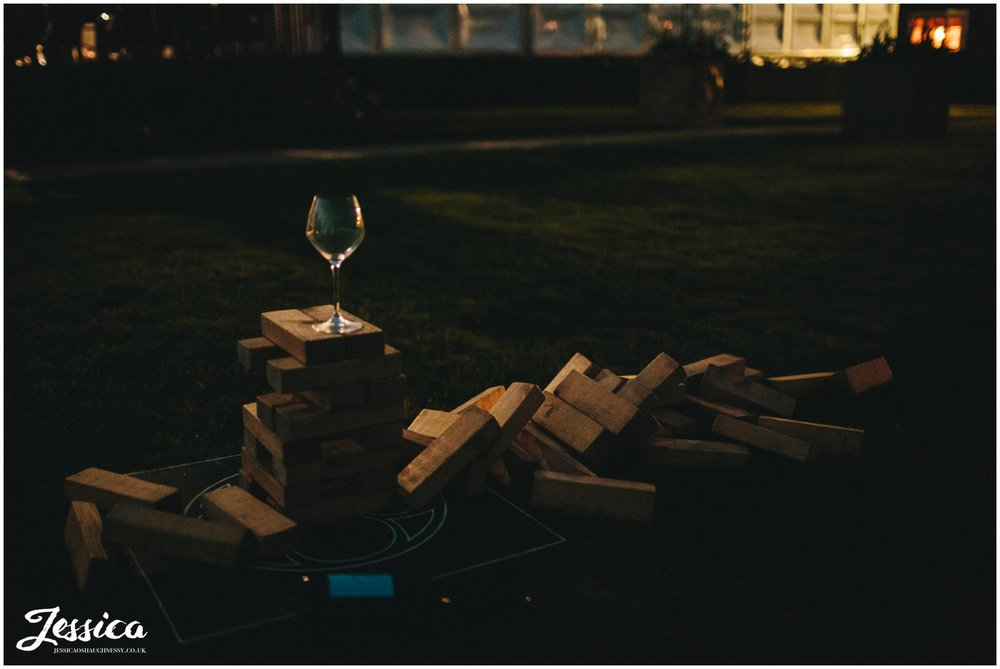 wine glass balances on jenga after a wedding at Combermere Abbey