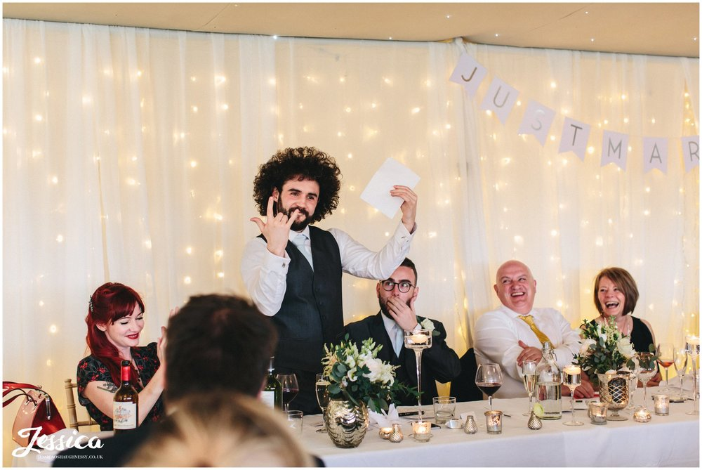 best man plays up to guests during his speech