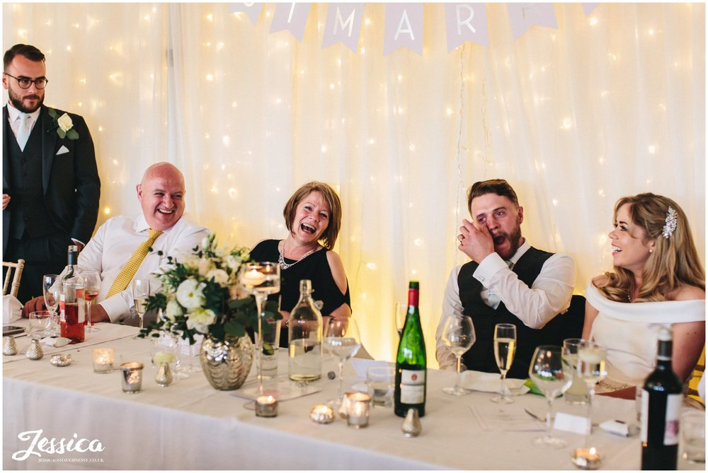 Combermere Abbey wedding photographer - top table laugh during best man's speech