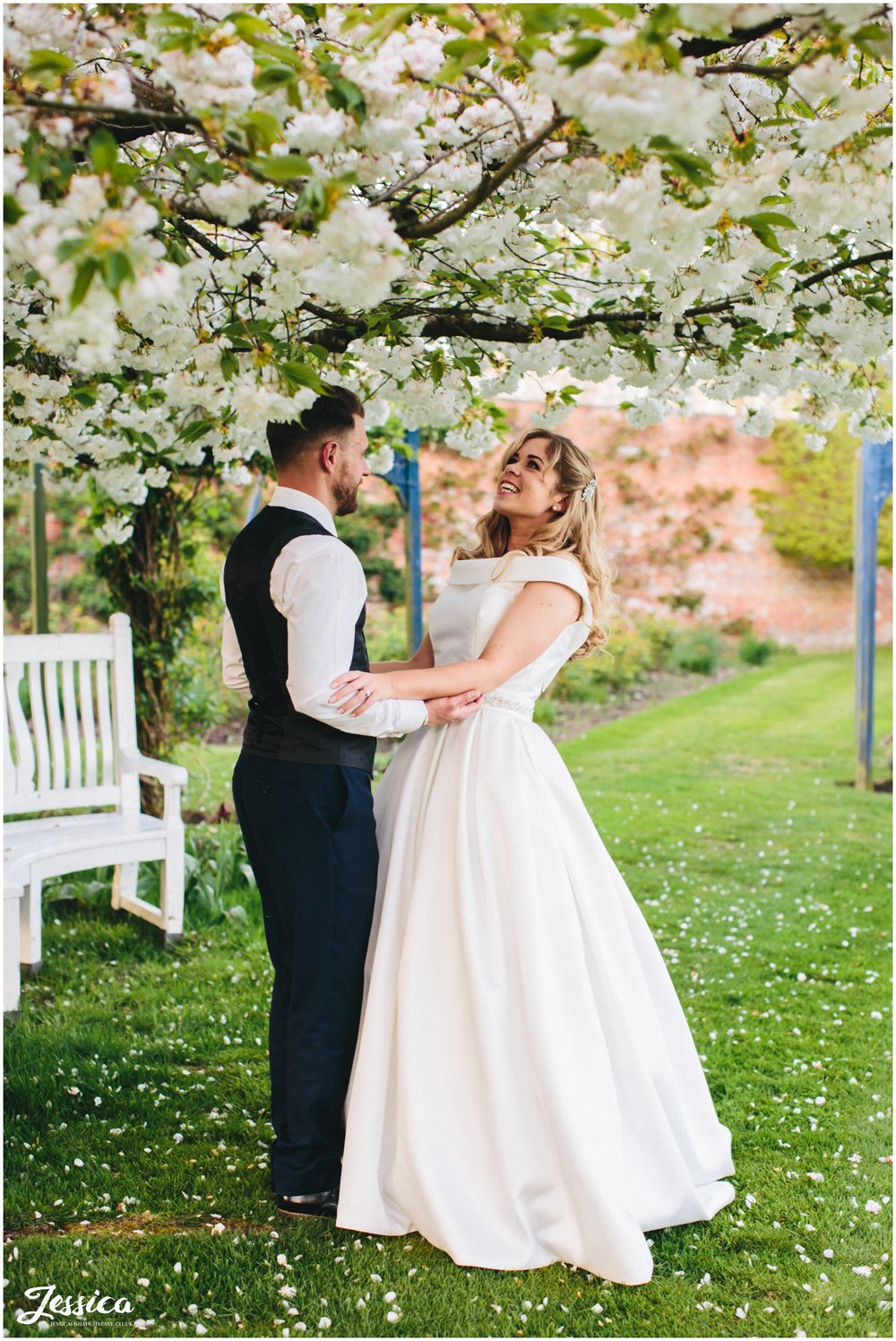 bride & groom under the Combermere Abbey blossom trees in shropshire
